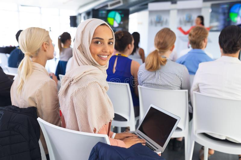 Happy Businesswoman using laptop during business seminar. Portrait of happy caucasian Businesswoman using laptop during business seminar . International diverse royalty free stock photos