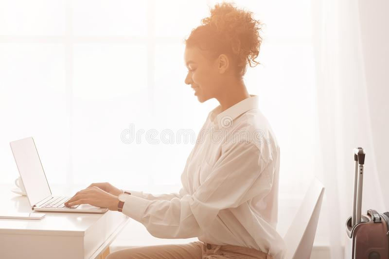 Happy businesswoman using laptop with suitase beside her royalty free stock photography