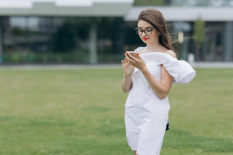 Happy businesswoman using smartphone wearing in blue shirt and glasses. Cheerful attractive young businesswoman in royalty free stock photo