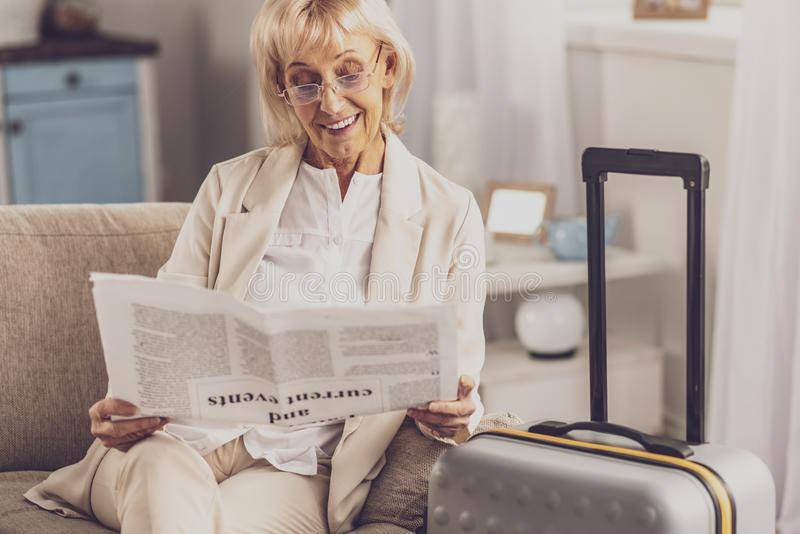 Happy businesswoman waiting for new trip. Relaxed atmosphere. Delighted blonde expressing positivity while reading newspaper royalty free stock photos