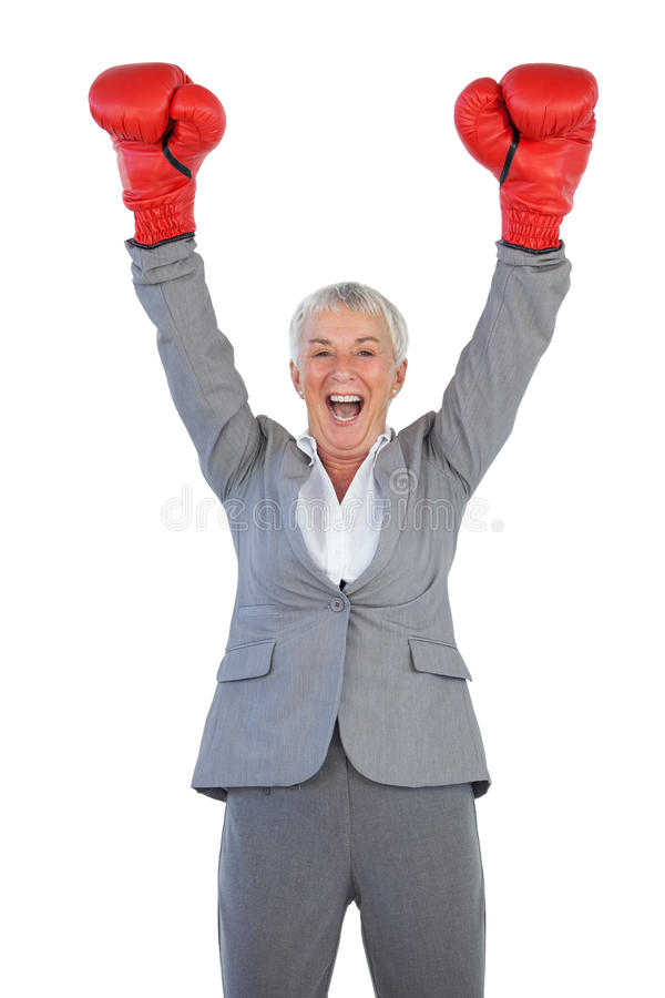 Happy businesswoman wearing boxing gloves and raising her arms royalty free stock photo