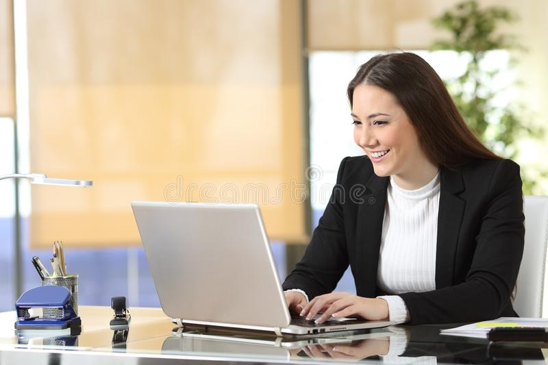 Happy businesswoman writing on laptop at office stock photos