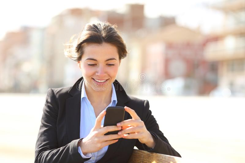 Happy busineswoman texting on phone in a park. Happy busineswoman texting on smart phone sitting on a bench in a park royalty free stock images