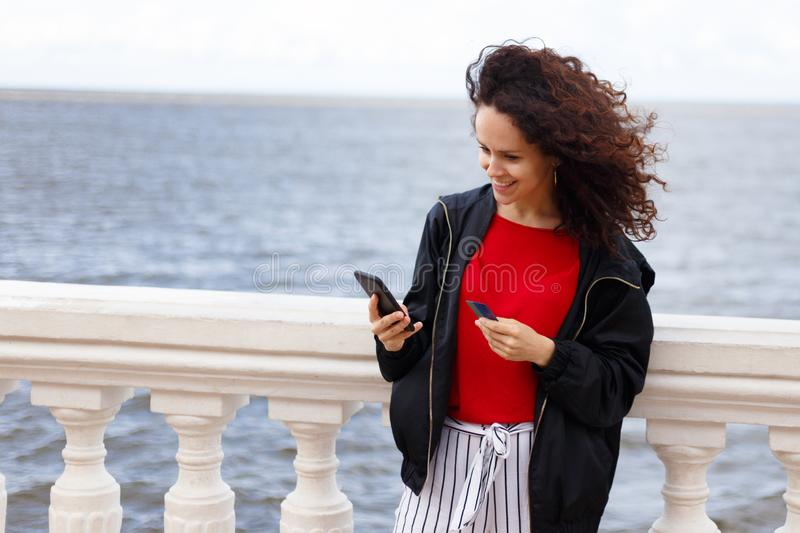 Happy buyer buys on line with credit card and phone, sitting in port, isolated on a seascape background. Copy space. stock photos