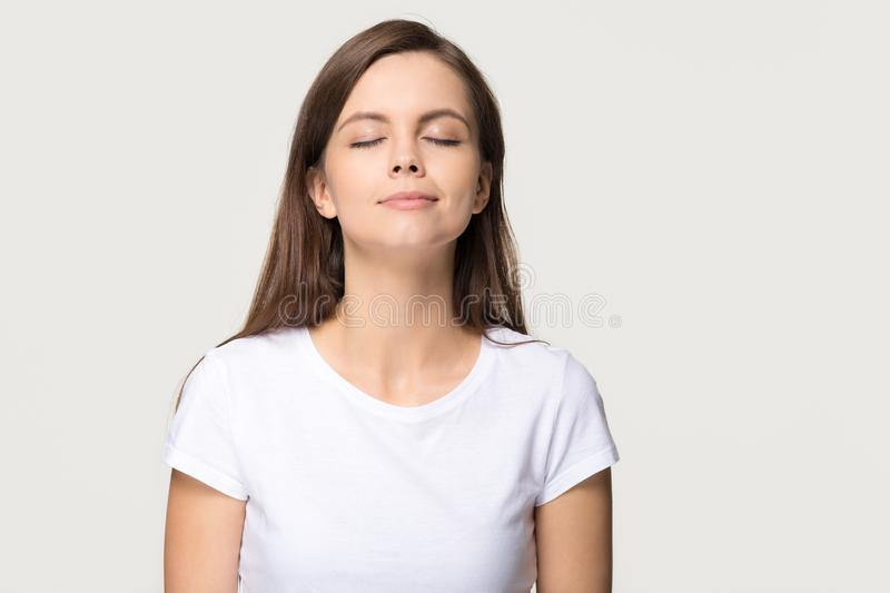 Happy calm girl enjoying good smell breathing fresh air isolated royalty free stock photography