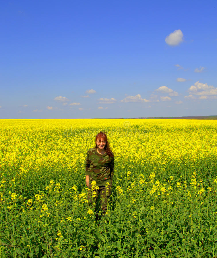 Smiling woman enjoying spring yellow fields. Vivid yellow spring fields against clear blue sky and military style dressed woman in the fields enjoying it royalty free stock photography