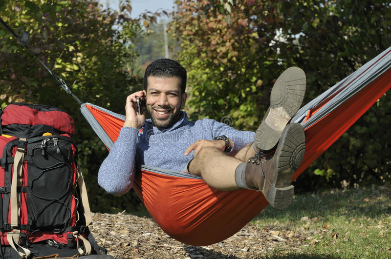 Happy Camper Chatting on Phone in a Hammock stock photography