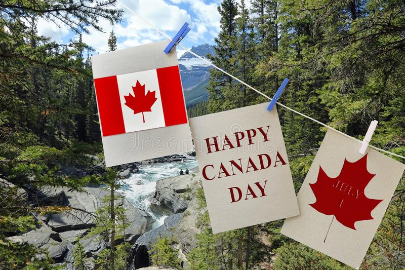 Happy Canada Day. Holiday greeting cards with Maple leaf and Canadian flag. Signs hanging on rope against beautiful Canadian landscape of Canadian Rockies and stock photo