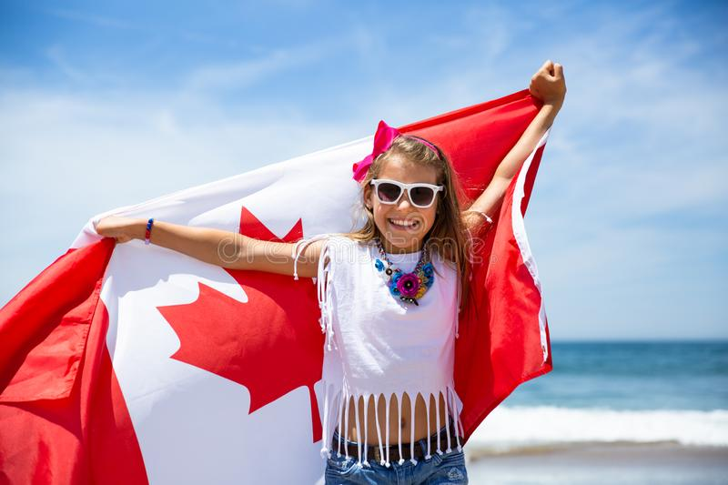 Happy Canadian girl carries fluttering white red flag of Canada against blue sky and ocean background. stock photos