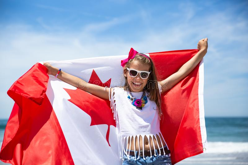 Happy Canadian girl carries fluttering white red flag of Canada against blue sky and ocean background. stock image
