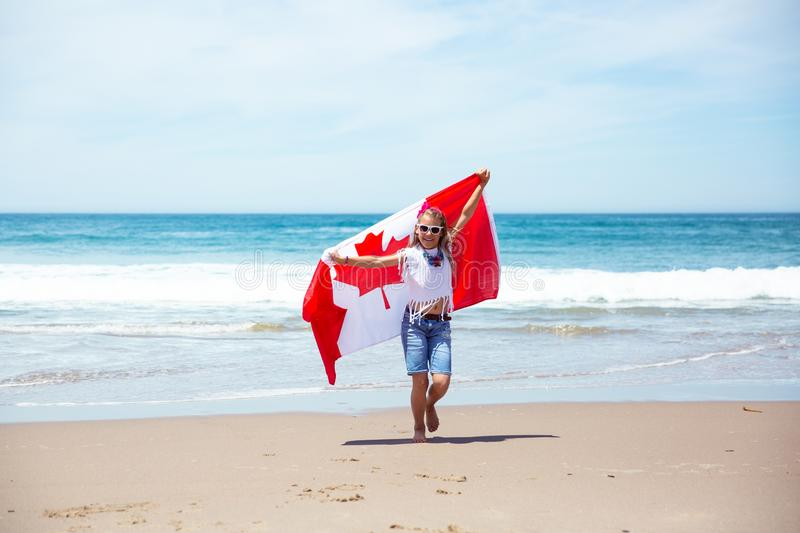 Happy Canadian girl carries fluttering white red flag of Canada against blue sky and ocean background. royalty free stock image