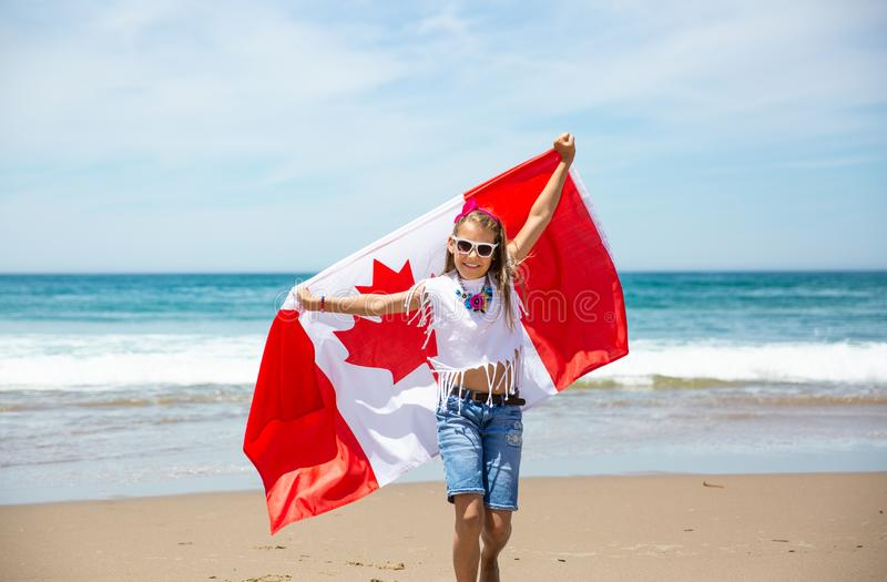 Happy Canadian girl carries fluttering white red flag of Canada against blue sky and ocean background. stock photography
