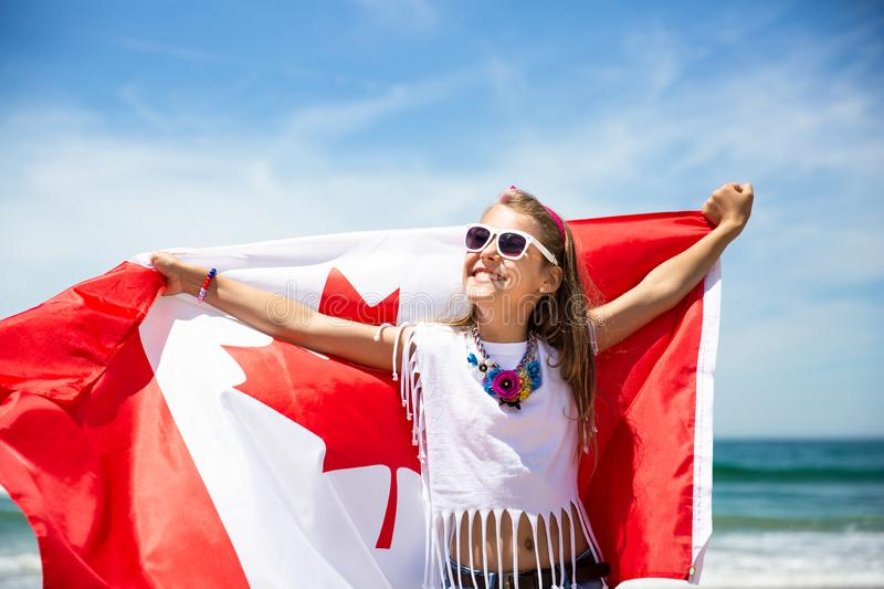 Happy Canadian girl carries fluttering white red flag of Canada against blue sky and ocean background. royalty free stock photo
