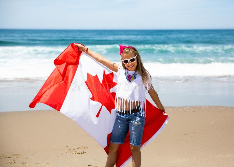Happy Canadian girl carries fluttering white red flag of Canada against blue sky and ocean background. royalty free stock photography