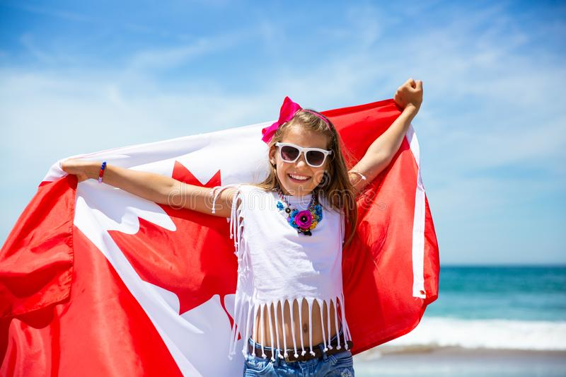 Happy Canadian girl carries fluttering white red flag of Canada against blue sky and ocean background. royalty free stock images