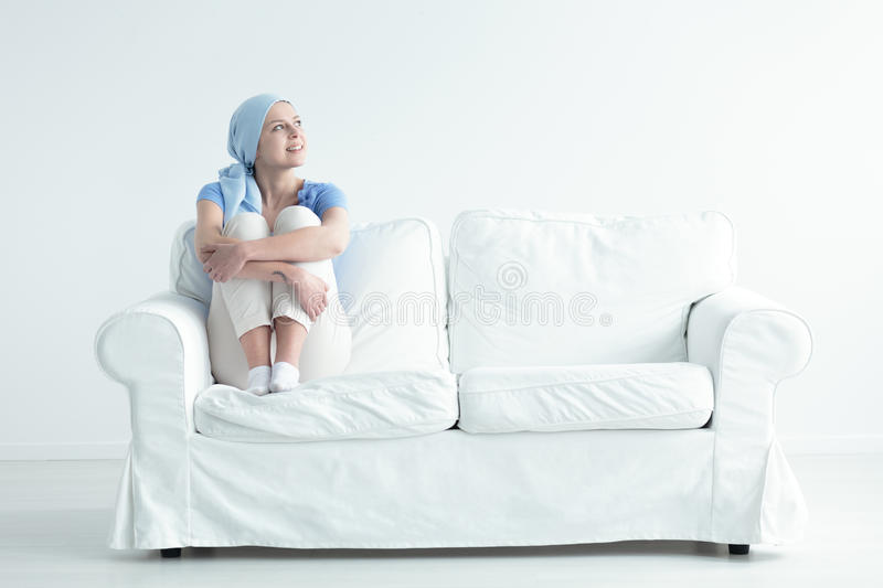 Happy cancer patient. Feeling relieved and holding her knees on a white sofa