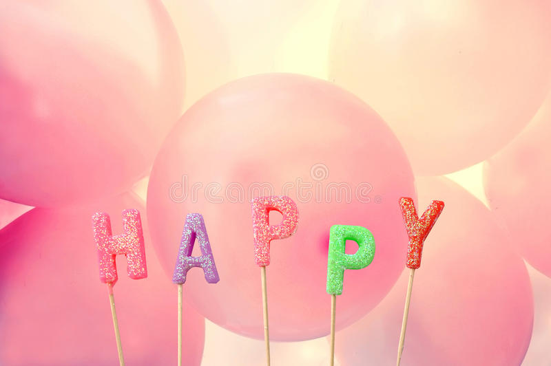 Happy candle letters with colourful balloons in the background.  royalty free stock image