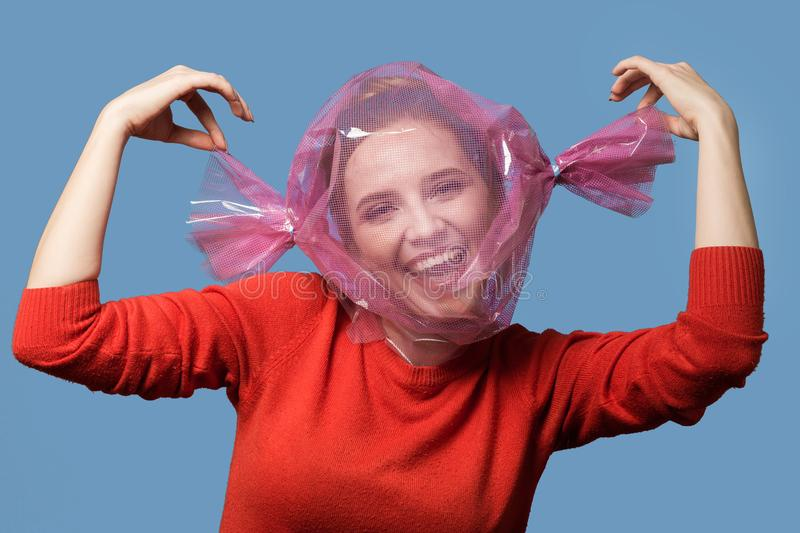 Happy candy girl. Fun girl with head inside candy wrapper on blue background royalty free stock photo