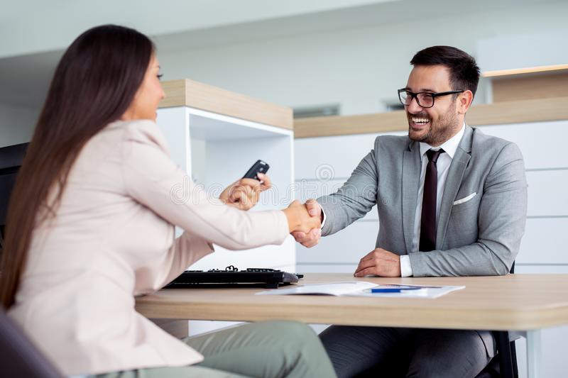 Happy car dealer and customer shake hands after successfully signed contract. Happy young car dealer and customer shake hands after successfully signed contract stock image