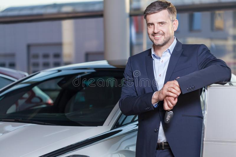 Happy car dealership client. Portrait of happy car dealership client with his new auto royalty free stock photo