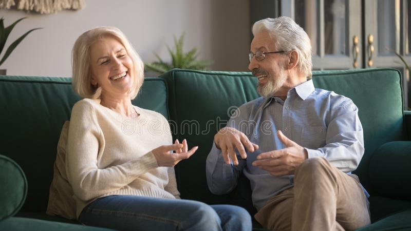 Excited happy family couple spending time together, laughing and joking. Happy carefree excited elderly family couple laughing, joking, talking, sharing good royalty free stock images