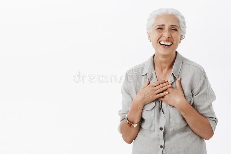 Happy carefree old woman satisfied with how life going. Joyful charming senior lady with grey hair in loose shirt. Holding palms on chest and laughing feeling royalty free stock images