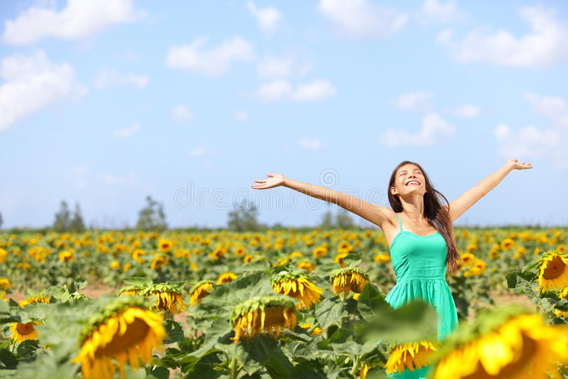Happy carefree summer girl in sunflower field. In spring. Cheerful multiracial Asian Caucasian young woman joyful, smiling with arms raised up stock photo