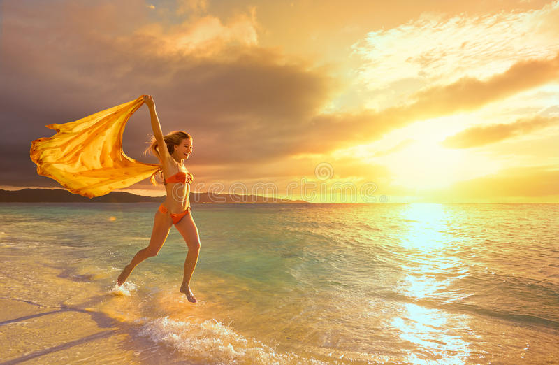Happy carefree woman running in the sunset on the beach. stock photos