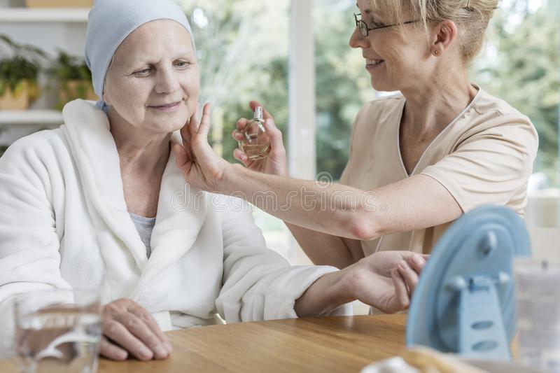 Happy caregiver spraying perfumes on sick senior woman with breast cancer. Happy caregiver spraying perfumes on sick senior women with breast cancer concept royalty free stock photography