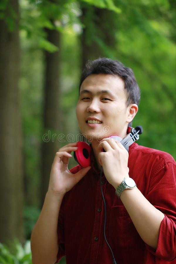 Happy careless free Asian Chinese man is listening to music and wearing a earphone royalty free stock photos