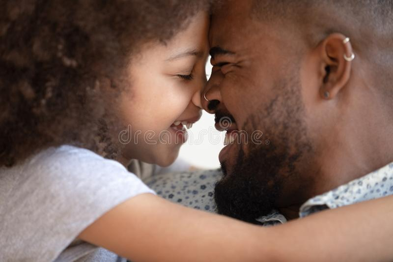 Happy caring african american man touching foreheads with smiling daughter. royalty free stock images