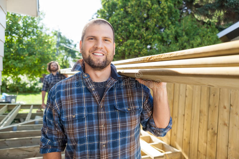 Happy Carpenter And Coworker Carrying Lumbers At. Portrait of happy carpenter and coworker carrying lumbers on shoulders at construction site royalty free stock image