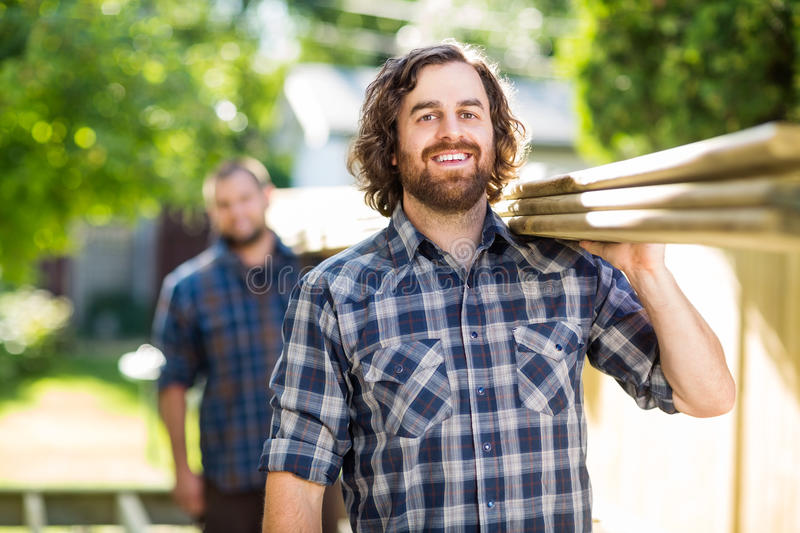 Happy Carpenter With Coworker Carrying Planks. Portrait of happy mid adult carpenter with coworker carrying wooden planks outdoors stock photography