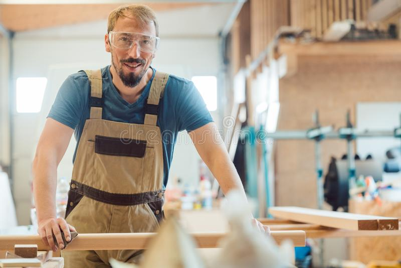 Happy carpenter in his wood workshop royalty free stock image