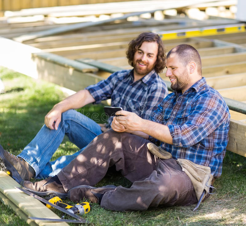 Happy Carpenters Looking At Mobile Phone At. Full length of happy mid adult carpenters looking at mobile phone at construction site royalty free stock images