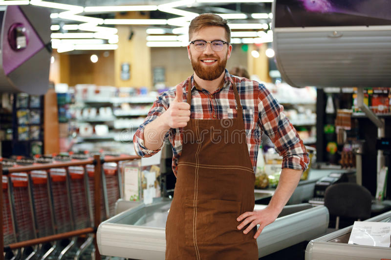 Happy cashier man on workspace shop showing thumbs up. Picture of happy cashier man on workspace in supermarket shop. Looking at camera showing thumbs up stock photo