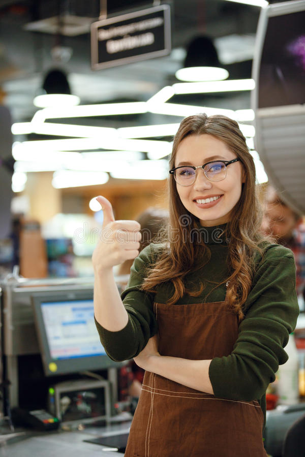 Happy cashier woman on workspace showing thumbs up. Photo of happy cashier woman on workspace in supermarket shop. Looking at camera showing thumbs up stock photo