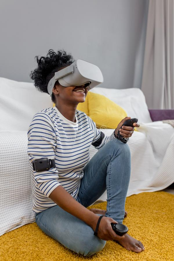 African woman watching video using VR glasses with remote control at home. royalty free stock photos