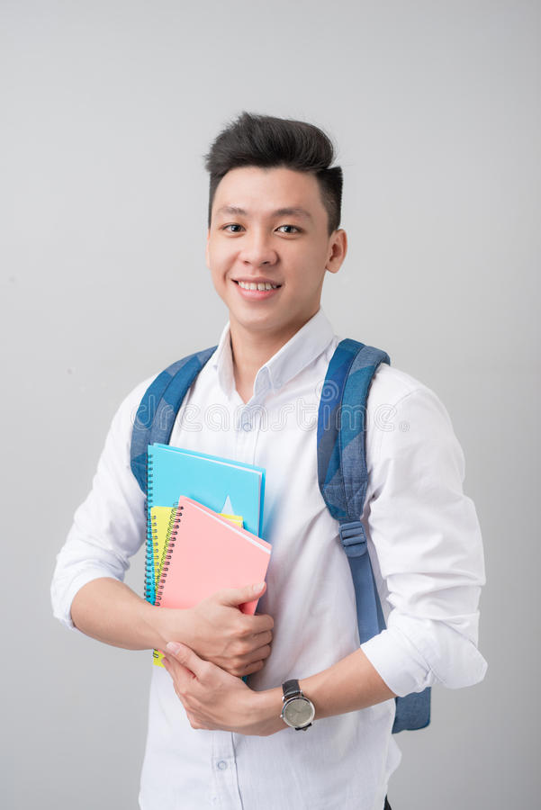 Happy casual asian male student holding books isolated on a gray stock images