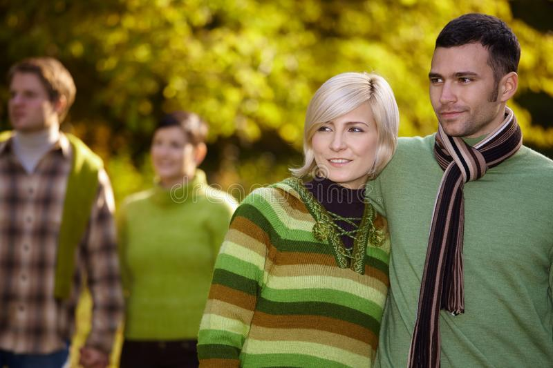 Happy casual couple with friends walking outdoor stock photo