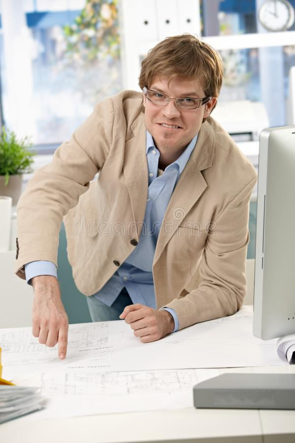 Happy casual engineer pointing at plan on table stock photography