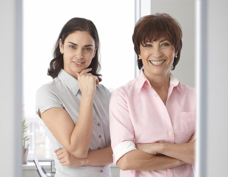 Happy casual female business office workers. Happy casual caucasian female business office workers, standing, smiling, looking at camera, hand under chin, arms royalty free stock images