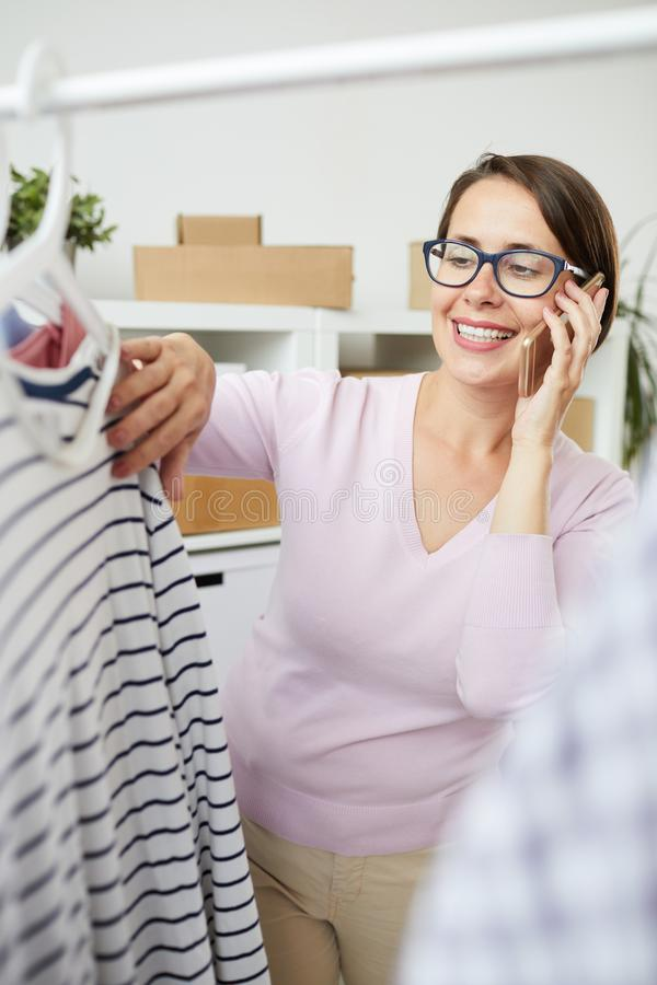 Happy casual female with smartphone looking through new seasonal collection stock photography