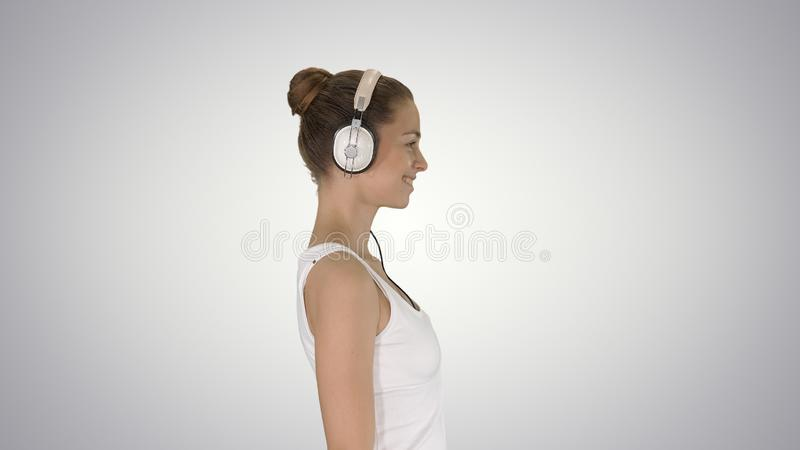 Happy casual girl wearing headphones walking on gradient background. royalty free stock photos