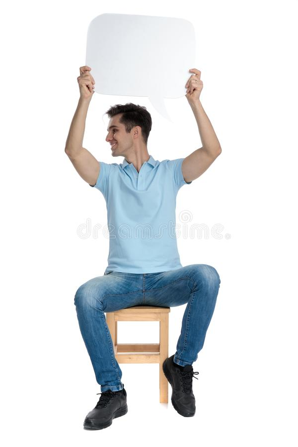 Happy casual guy holding an empty speech bubble. Above his head while looking to the side and smiling, sitting on a chair on white studio background stock image
