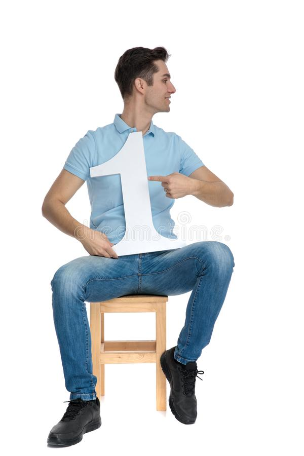 Happy casual guy pointing to his number one. And looking to the side while wearing blue jeans and sitting on a chair on white studio background stock photo