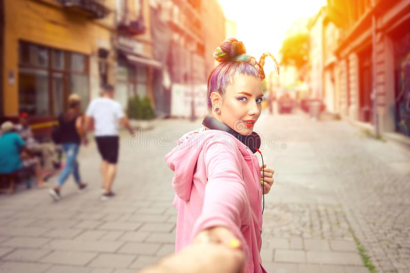 Happy casual hipster girl holding hand looking behind while walking on city street royalty free stock photos