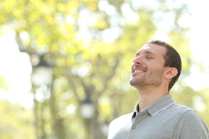 Happy casual man breathing fresh air in a park. With trees in the background stock image