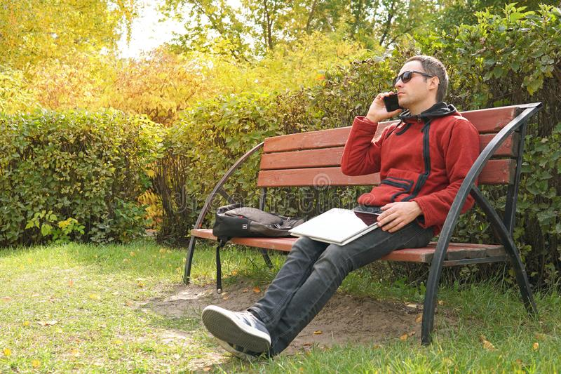 Happy casual man with laptop and take away coffee talking on mobile. Handsome male freelancer working outdoors in the stock photo