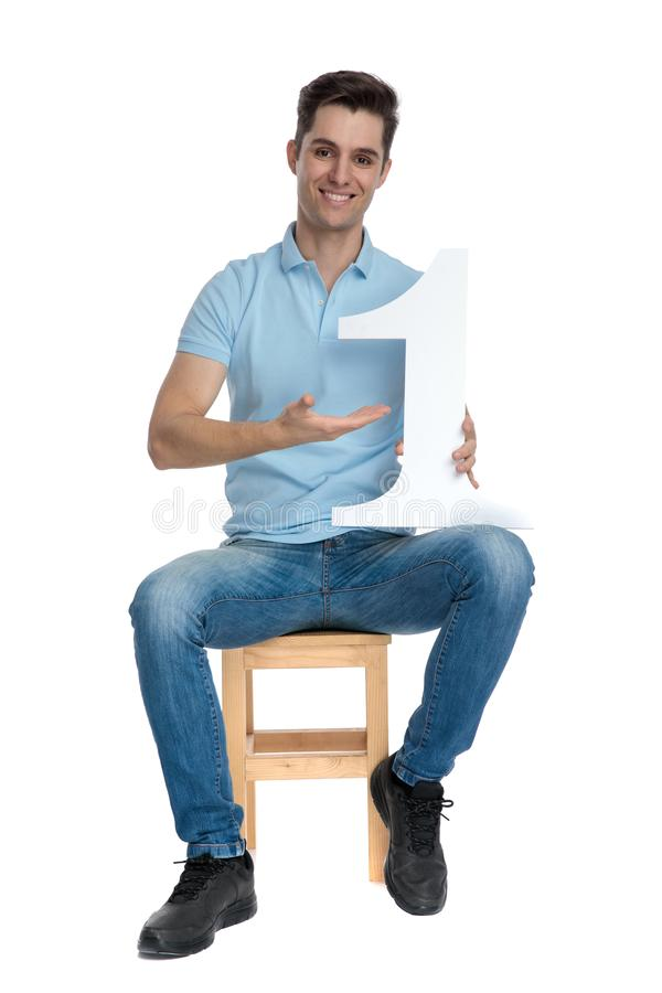 Happy casual man presenting his number one while smiling royalty free stock photography